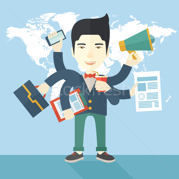 Young but happy japanese employee doing multitasking office tasks. Stock photo © RAStudio