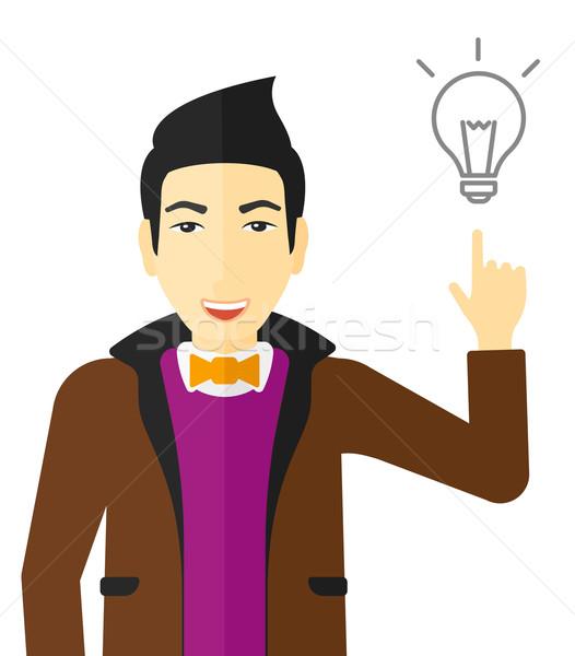 Man pointing at light bulb. Stock photo © RAStudio