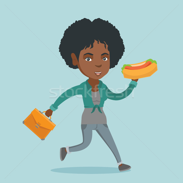 African business woman eating hot dog on the run Stock photo © RAStudio