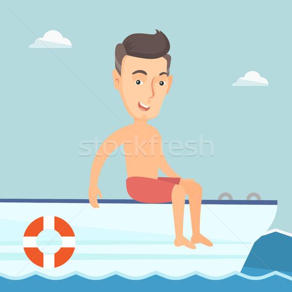 Young happy man tanning on a sailboat. Stock photo © RAStudio