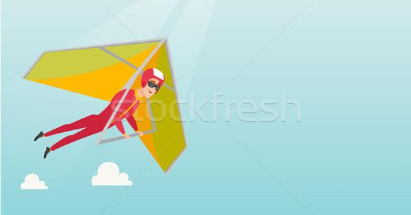 Young caucasian man flying on hang-glider. Stock photo © RAStudio