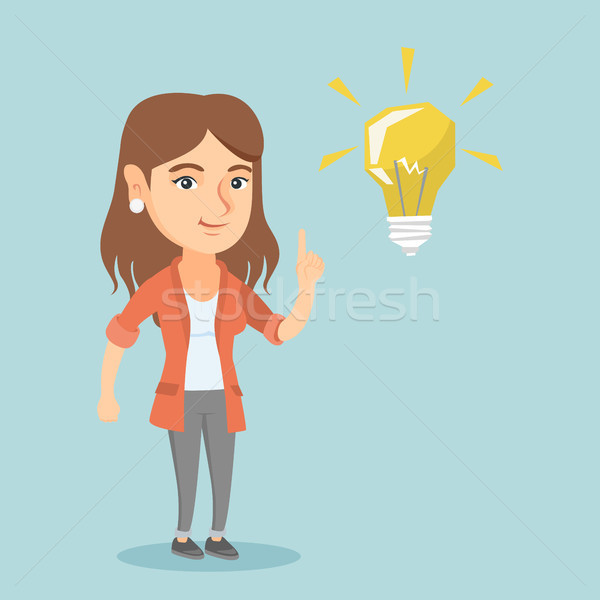 Young caucasian student pointing at idea lightbulb Stock photo © RAStudio