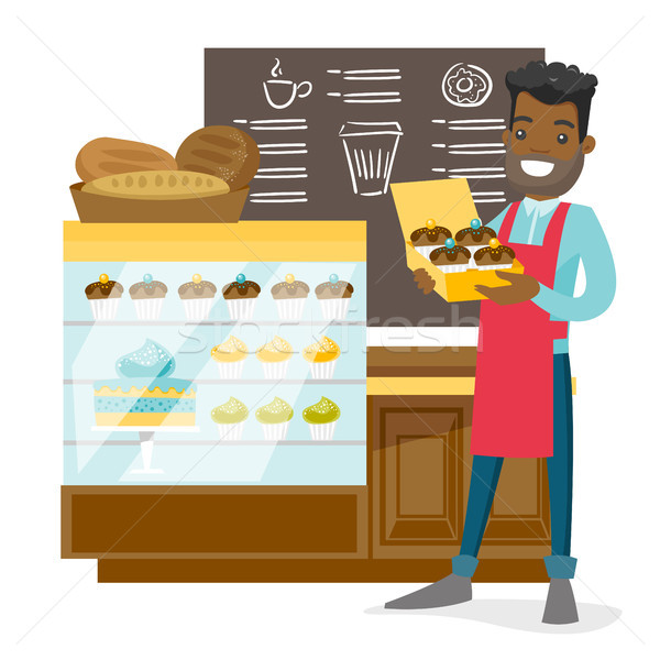 Young worker of the bakery offering cupcakes. Stock photo © RAStudio