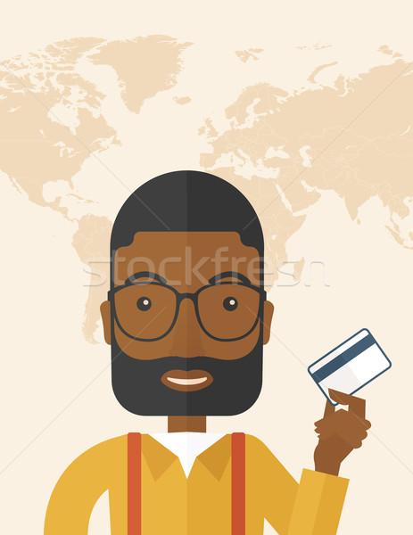 Happy businessman standing holding credit card. Stock photo © RAStudio