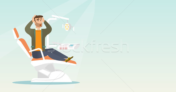 Afraid man sitting in the dental chair. Stock photo © RAStudio