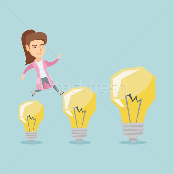 Caucasian business woman jumping on light bulbs. Stock photo © RAStudio
