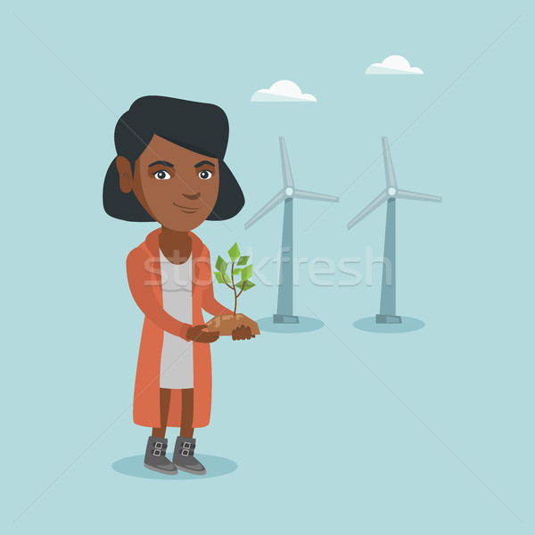 African worker of wind farm holding small plant. Stock photo © RAStudio