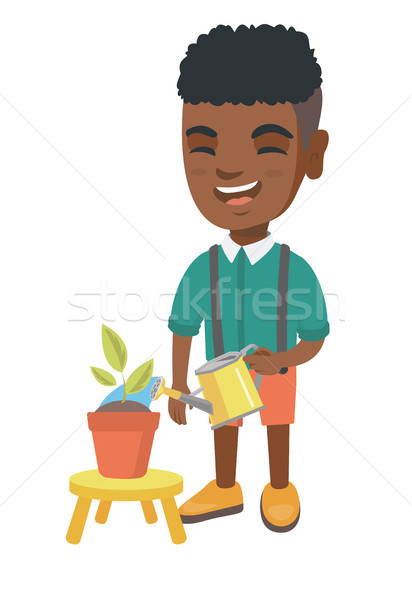 African boy watering plant with a watering can. Stock photo © RAStudio