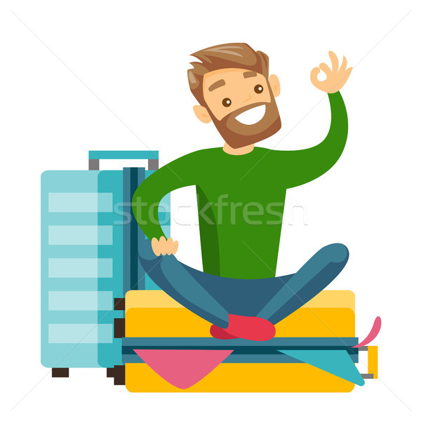 Young caucasian white man sitting on suitcase. Stock photo © RAStudio