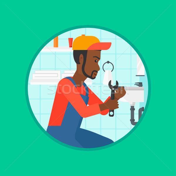 Plumber fixing sink pipe with wrench. Stock photo © RAStudio