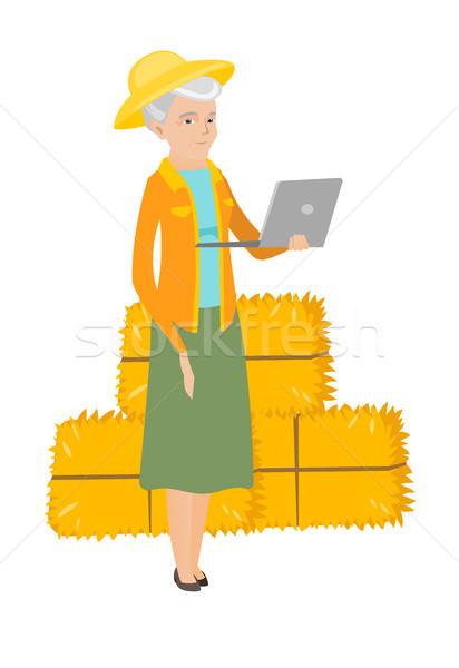 Senior caucasian farmer using a laptop. Stock photo © RAStudio