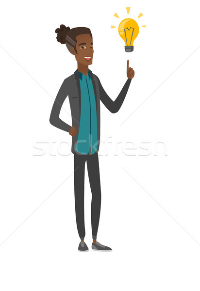 African businessman pointing at idea lightbulb. Stock photo © RAStudio