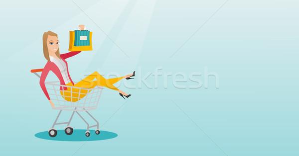 Young caucasian woman riding in shopping trolley. Stock photo © RAStudio