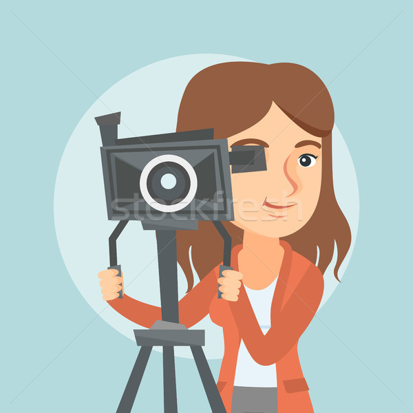 Caucasian cameraman with movie camera on tripod. Stock photo © RAStudio
