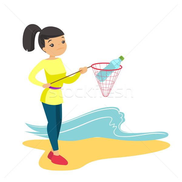 Woman catching plastic bottle from sea water. Stock photo © RAStudio