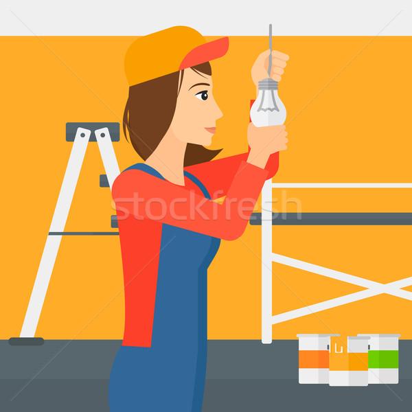 Electrician twisting light bulb. Stock photo © RAStudio