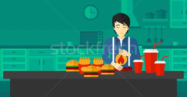 Man lijden maagzuur asian permanente keukentafel Stockfoto © RAStudio