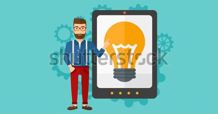 Man pointing at tablet computer with light bulb on screen. Stock photo © RAStudio