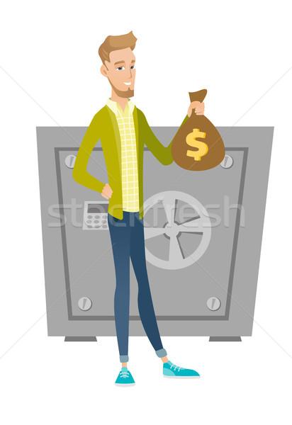 Fiatal kaukázusi üzletember tart pénz táska Stock fotó © RAStudio
