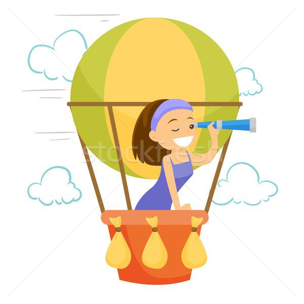 Caucasian white woman flying in hot air balloon. Stock photo © RAStudio