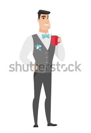 Young caucasian groom holding cup of coffee. Stock photo © RAStudio