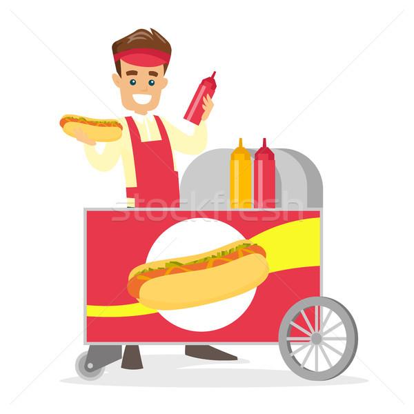 Caucasian white street seller making a hot dog. Stock photo © RAStudio