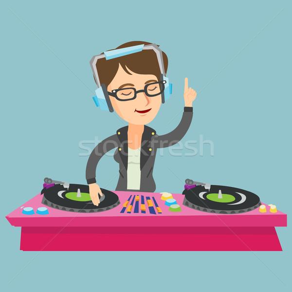 Young caucasian DJ mixing music on turntables. Stock photo © RAStudio