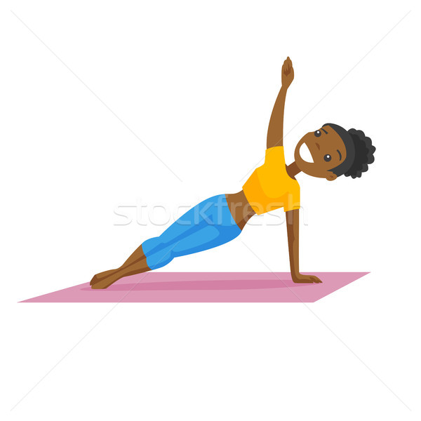 Young african-american woman holding a side plank. Stock photo © RAStudio