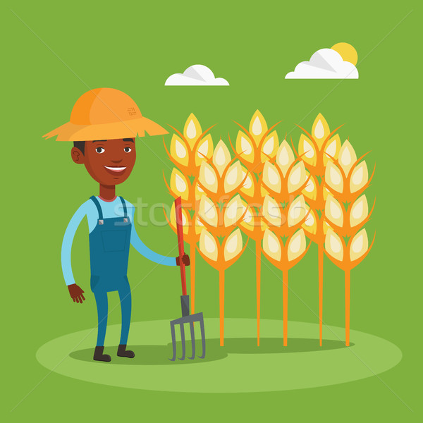 Farmer with pitchfork at wheat field. Stock photo © RAStudio