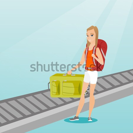 Woman picking up suitcase on luggage conveyor belt Stock photo © RAStudio