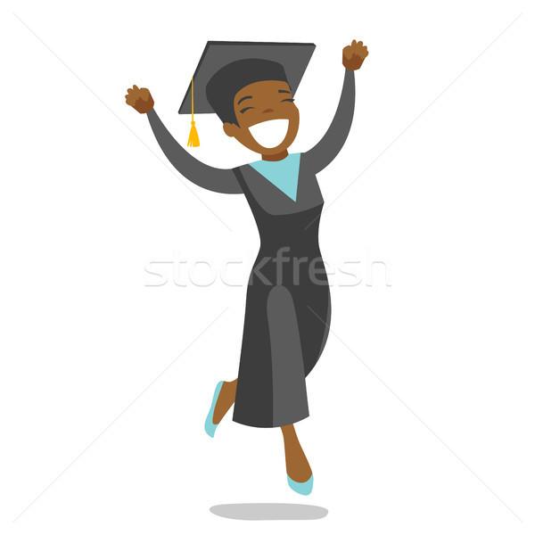 Young cheerful african-american graduate jumping. Stock photo © RAStudio