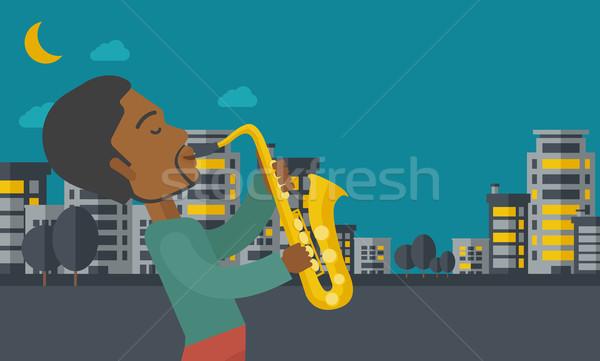 Zenész játszik szaxofon utcák éjszaka vektor Stock fotó © RAStudio