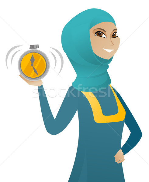 Young muslim business woman holding alarm clock. Stock photo © RAStudio