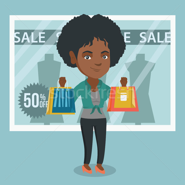 Young african-american woman shopping on sale. Stock photo © RAStudio