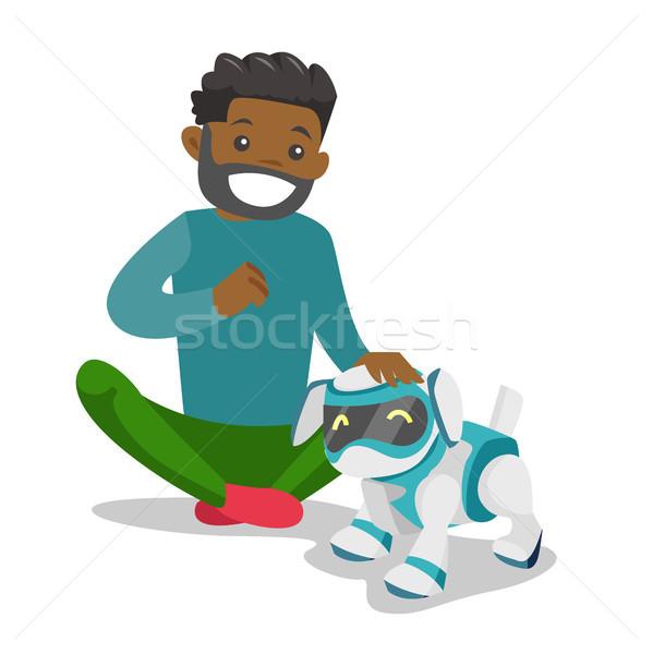 Siyah adam oynama köpek robot mutlu Stok fotoğraf © RAStudio