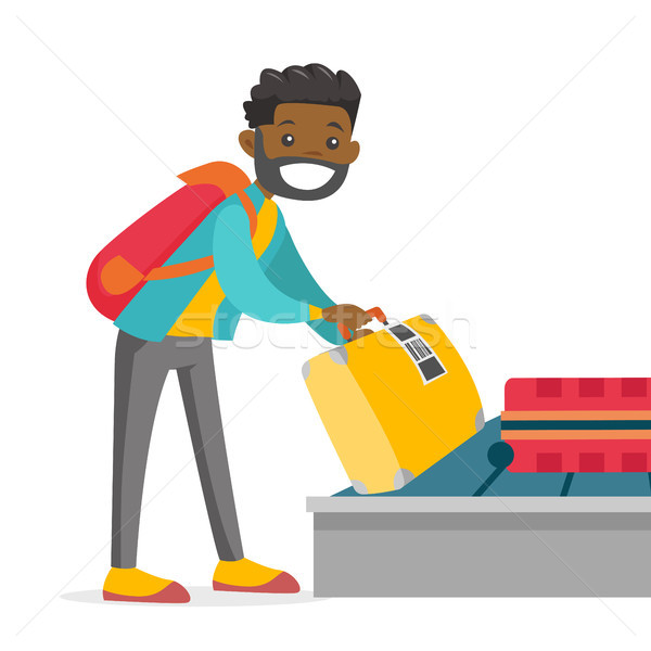 A man taking his case in baggage claim of the airport. Stock photo © RAStudio