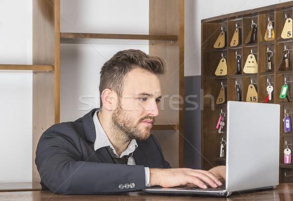 Recepcionista trabalhando laptop secretária pequeno albergue Foto stock © RazvanPhotography