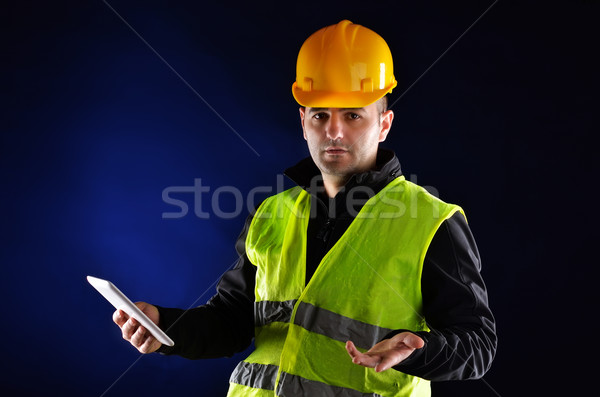 Stock photo: Young engineering with orange helmet working on a tablet pc