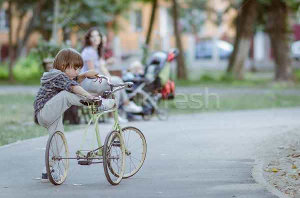 Stock photo: Happy boy with bicycle in the autumn park