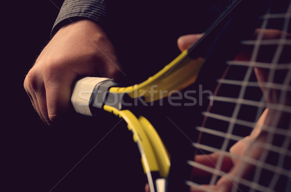 Hand on grip and swinging a tennis racket. Isolated on black bac Stock photo © razvanphotos