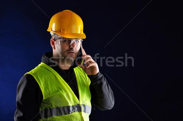 Young engineering with orange helmet talking on the phone Stock photo © razvanphotos