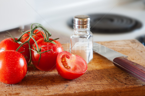 Fresh tomatoes on a cutting board with a knife and salf. Stock photo © rcarner