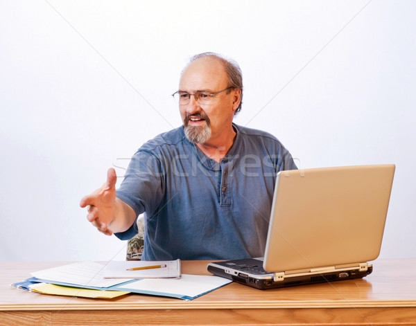 Businessman reaching out to shake a clients hand. Stock photo © rcarner