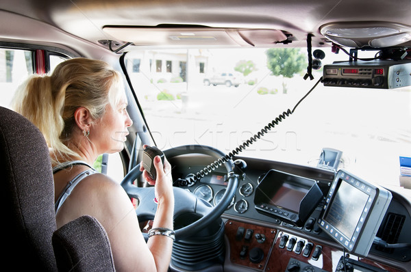 Blonde woman truck driver talking on her radio. Stock photo © rcarner