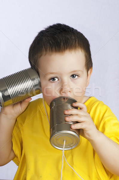 Little boy with tin cans and string for a walkie-talkie. Stock photo © rcarner