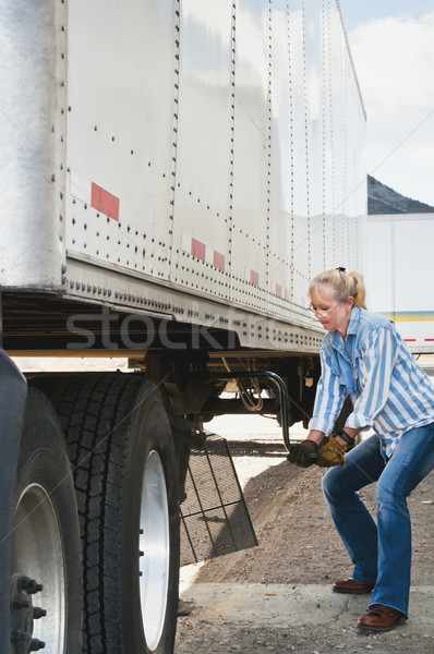 Woman Truck Driver Raising Trailer legs Stock photo © rcarner