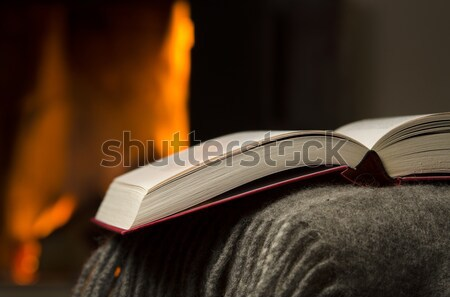 Stock photo: Open book by fireplace.