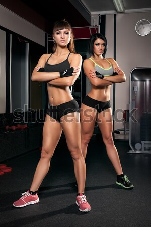 Fitness woman with barbells on grey background Stock photo © restyler
