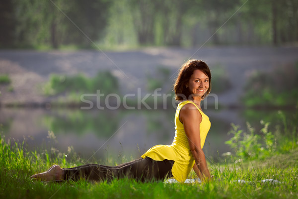 woman performs yoga exercises and Pilates in nature Stock photo © restyler