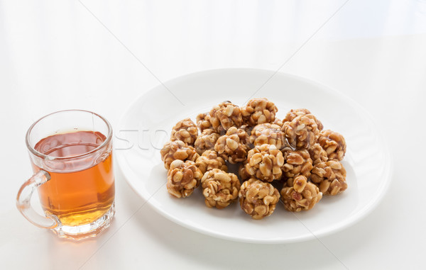 Sweet peanut balls in a plate and glass of black tea Stock photo © robinsonthomas